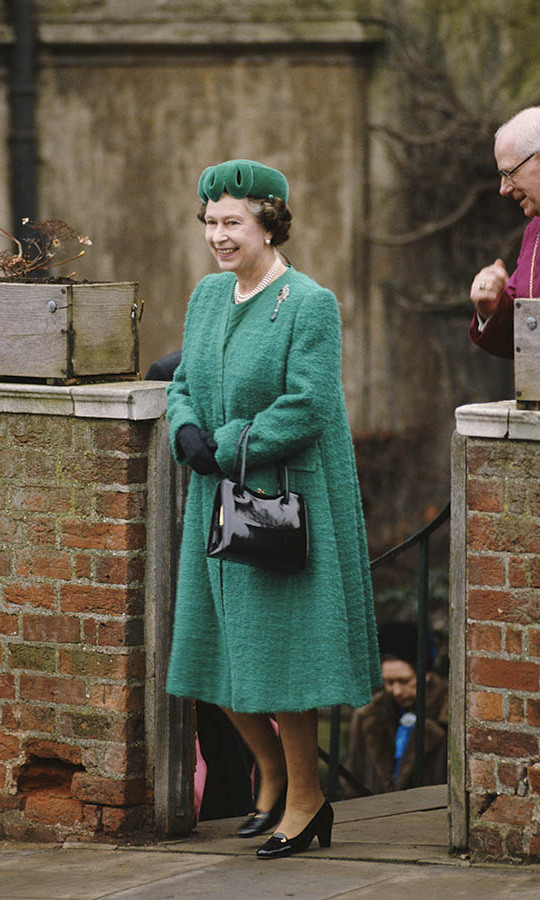 In 1988, the Queen dazzled in emerald green at Easter service at St. George's Chapel. She topped off her long coat with a striking hat with swirled front. As per usual, she accessorized with her black loafers and handbag!