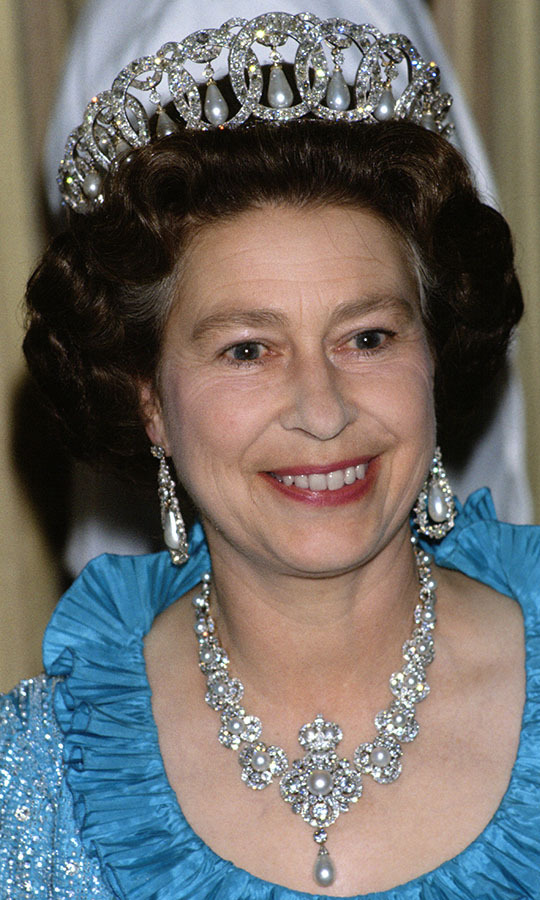 Beauty in blue! Her Majesty enchanted at a state banquet during a royal tour of Switzerland in 1980 in the diamond-and-pearl option of the Vladimir tiara, her often-seen pearl and diamond earrings and the diamond-and-pearl Golden Jubilee necklace.