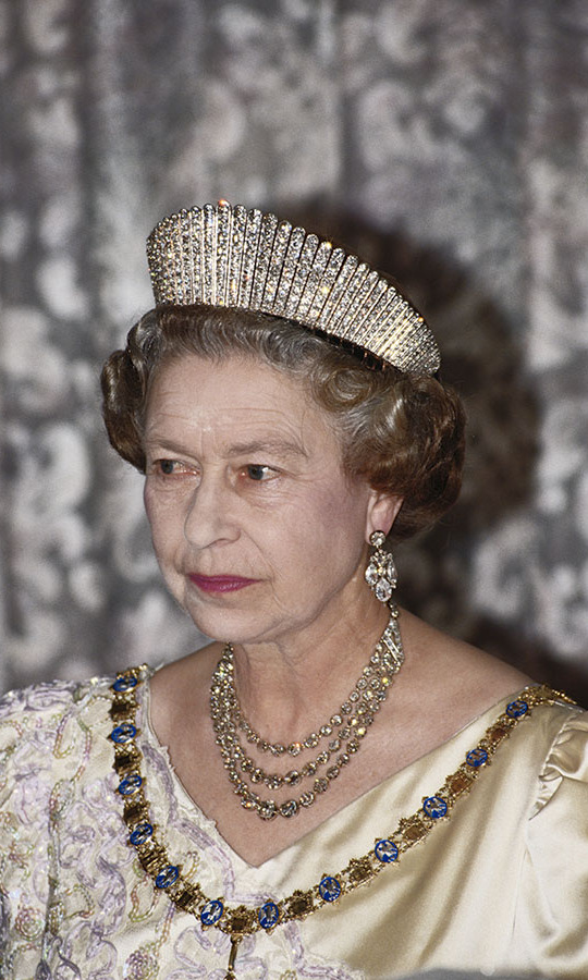 The regal monarch sported the rarely seen Russian fringe diamond tiara while attending a state banquet in Reykjavik during a three-day trip to Iceland in 1990.