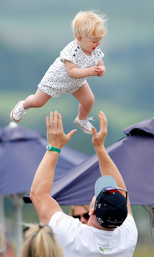 Higher! Mike threw Lena in the air during a family outing. Look at the joyful expression on her face.