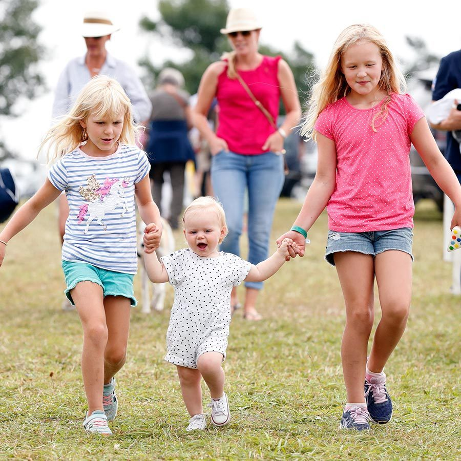 All together now! <a href=/tags/0/isla-phillips><strong>Isla</strong></a> and <a href=/tags/0/savannah-phillips><strong>Savannah Phillips</strong></a> were photographed helping young cousin Lena walk at the 2019 Festival of British Eventing at Gatcombe Park. They looked like they were having a ball enjoying the sunny summer weather.