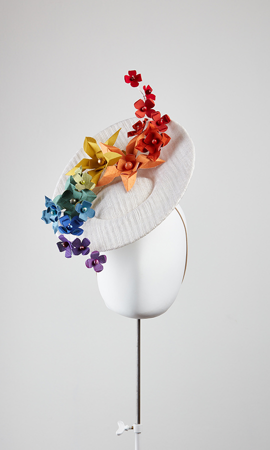 """I used my signature origami flowers and worked them in toning rainbow colours – I wanted the flowers to look like they were floating, or had just rested on the hat,"" the designer explained of her finished hat.