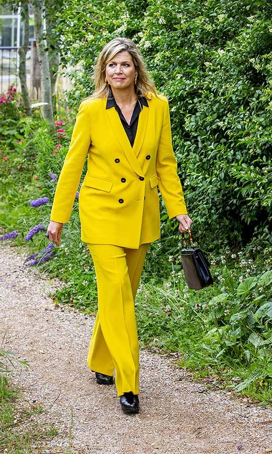 Here comes the sunny yellow! On July 8, <a href=/tags/0/queen-maxima><strong>Queen Maxima</strong></a> of the Netherlands stopped by a climbing forest, Zeeuwse Helden, and Ons Buiten camp in Burgh-Haamstede. She wore a double-breasted yellow pantsuit with black blouse, black ankle booties and handbag. Gold hoops completed the striking ensemble.
