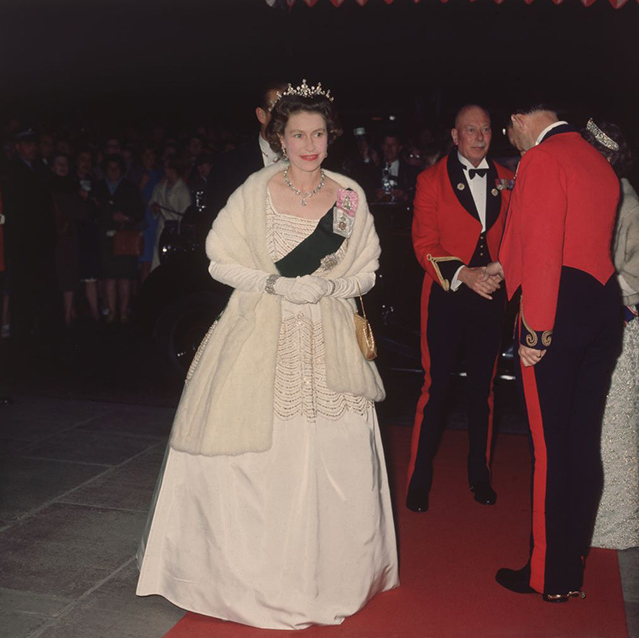 Her Majesty captivated with every footstep at a film premiere in 1960 wearing a white beaded evening gown by Norman Hartnell. 