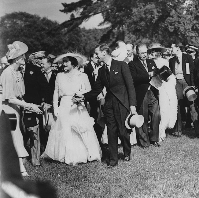 The future Queen Mother, pictured here with husband <a href=/tags/0/king-george-vi><strong>King George VI</strong></a> and then-French President <strong>Albert François Lebrun</strong>, donned a white Norman Hartnell design to a garden party at the Château de Bagatelle in the Bois de Boulogne, during the couple's state visit to Paris in July 1938. 