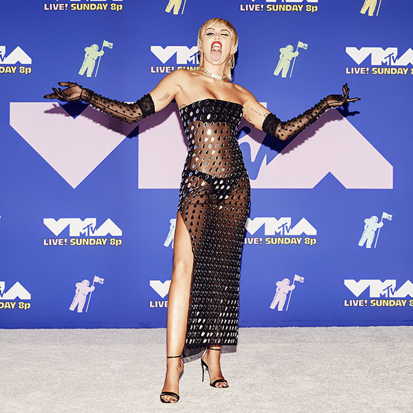 <a href=/tags/0/miley-cyrus><strong>Miley Cyrus</strong></a> commanded attention in a daring sheer dress decorated with paillettes paired with matching gloves.