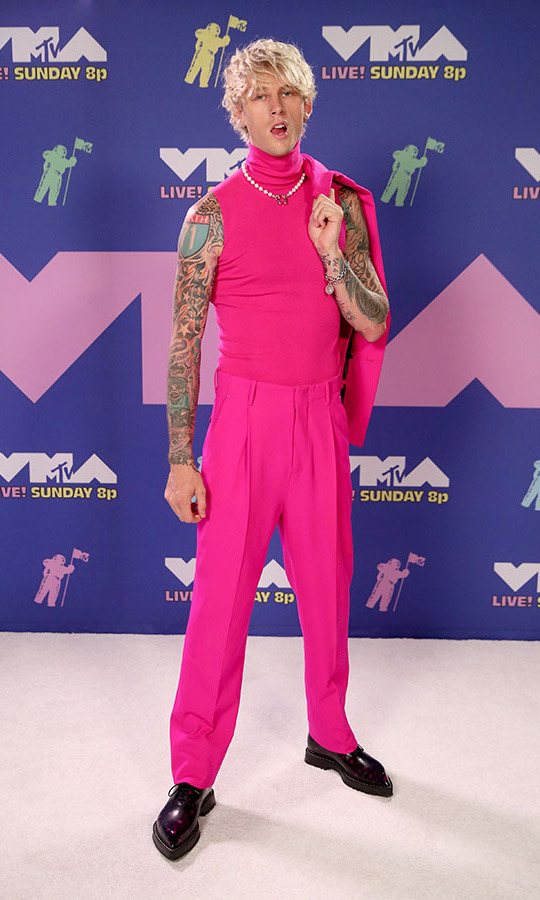<strong>Machine Gun Kelly</strong> embraced colour in a shocking pink three-piece ensemble from <strong>Berluti</strong> accessorized with black shoes and a pearly necklace.