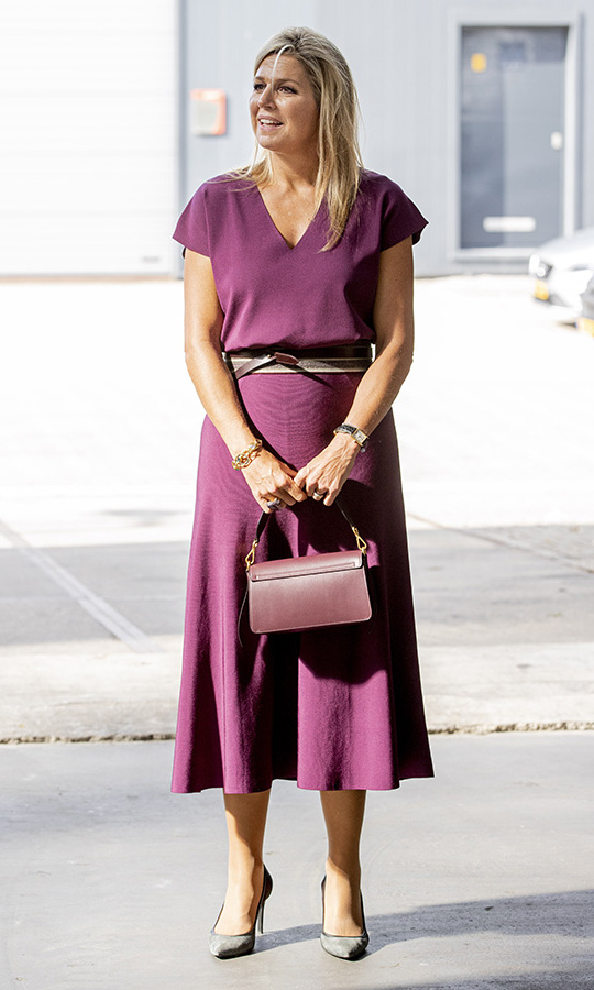 Queen Máxima mastered transitional dressing in a short-sleeved plum midi dress accessorized with matching bag and dark pumps. The Dutch queen wore the look on Sept. 10 to visit Doornbos Equipment in Rotterdam. It was the perfect thing for late summer/early autumn!