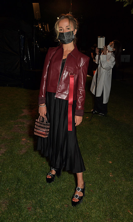 <a href=/tags/0/lady-amelia-windsor><strong>Lady Amelia Windsor</strong></a> attended an event during London Fashion Week on Sept. 19, wearing a burgundy biker jacket with red ribbon, a black pleated skirt, platform sandals and a dark non-surgical mask.
