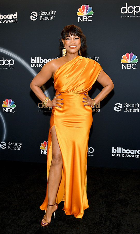 <strong>Garcelle Beauvais</strong> lit up the black carpet in a cheerful orange one-shouldered gown, bronze strappy sandals and gold jewelry.