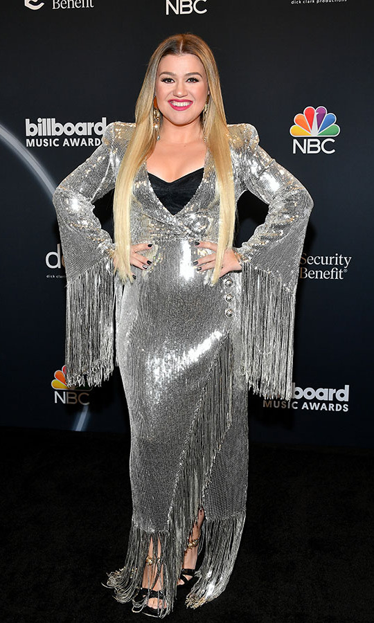 Host <a href=/tags/0/kelly-clarkson><strong>Kelly Clarkson</strong></a> struck a pose that showcased the trailing fringe of her silver <a href=/tags/0/balmain><strong>Balmain</strong></a> maxi dress.