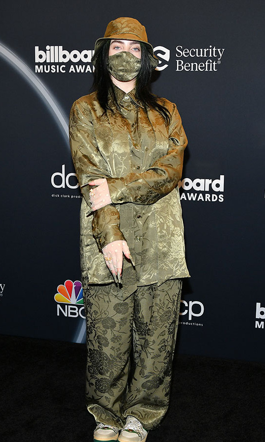 Billie Eilish, who took home three trophies at the 2020 Billboard Music Awards, was fully coordinated in an olive brocade look from <a href=/tags/0/gucci><strong>Gucci</strong></a> complete with bucket hat and face mask.