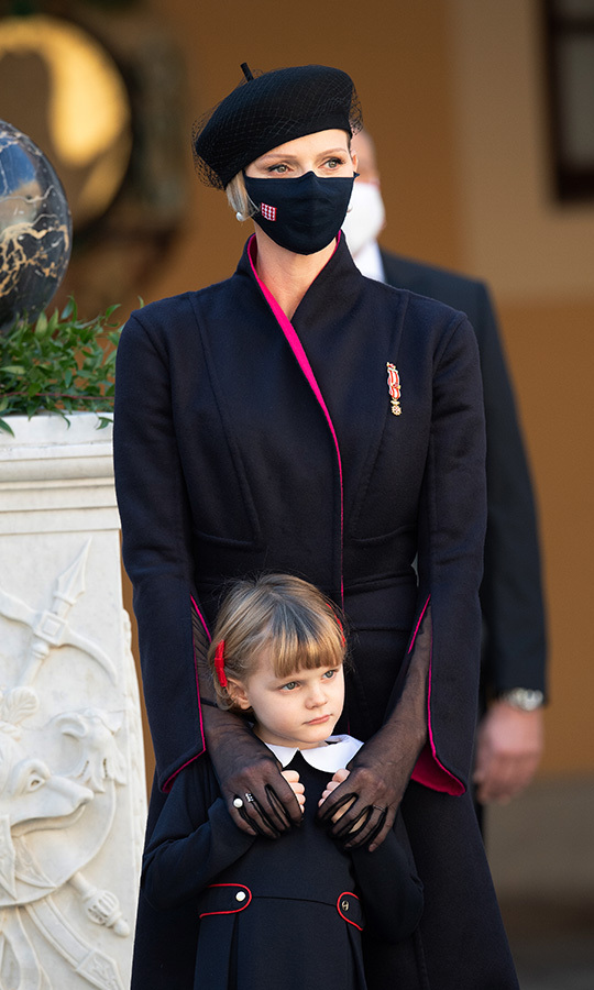 Charlene was sophisticated in a black wrap coat with contrasting pink lining. Her ensemble was topped with a black netted beret, black face mask and sheer black gloves.