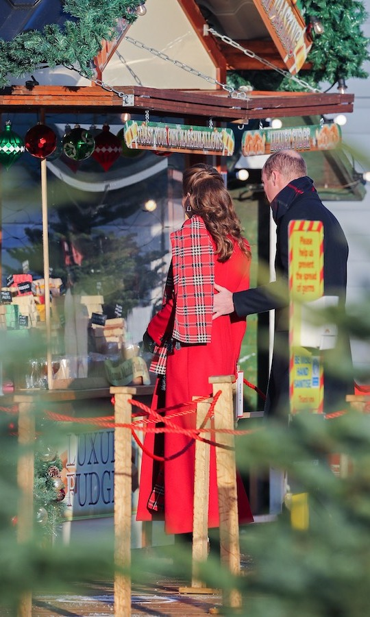 While waiting for their treats to roast, William engaged in a bit of subtle PDA and put his arm on Kate's back. 