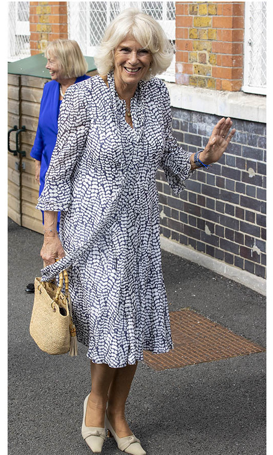 <a href=/tags/0/camilla-parker-bowles><strong>Duchess Camilla</strong></a> looked chic on Sept. 8 in a white-and-blue patterned dress with scarf detail at Ivydale Primary School in London.