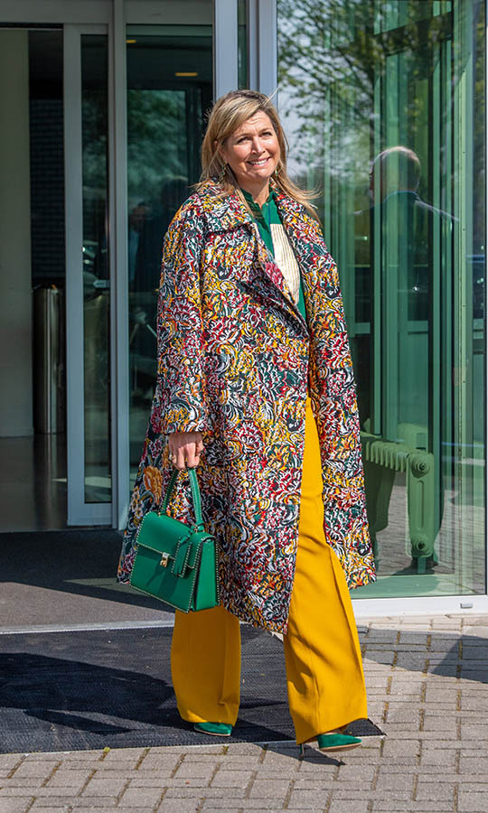 Queen Máxima brought joy in a multicoloured coat, mustard trousers and a green blouse, bag and heels when she visited Demcon, a technology company producing medical machines, in Enschede on April 16.