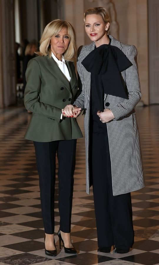 French First Lady <strong>Brigitte Macron</strong> welcomed Charlene and Albert to the Chateau de Versailles in 2018 to celebrate the 100th anniversary of the Armistice ending World War I. Charlene looked stunning in a black-and-white checked coat with a massive black bow. 