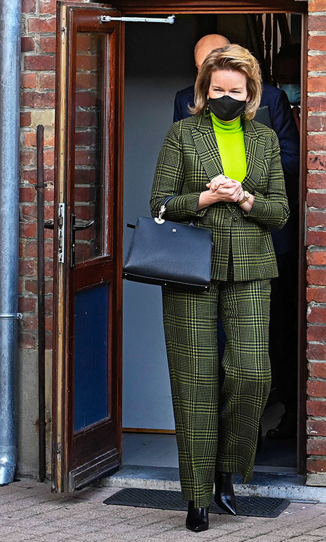 <a href=/tags/0/queen-mathilde><strong>Queen Mathilde</strong></a> of Belgium lit up the day in a black-and-green pantsuit and coordinating fluorescent turtleneck during a visit to the Toboggan Center for Girls and Young Mothers in Difficulty on Jan. 26, 2021 in Mons, Belgium.