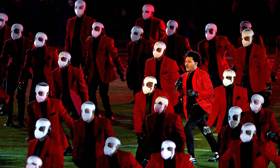"Next, a crew of The Weeknd's bandaged dancers took to the field for a stomping performance. He joined them to sing ""Blinding Lights.""