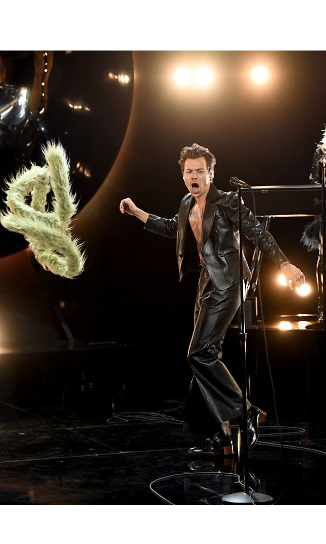 He threw away his sage green boa during the performance to reveal his leather suit.