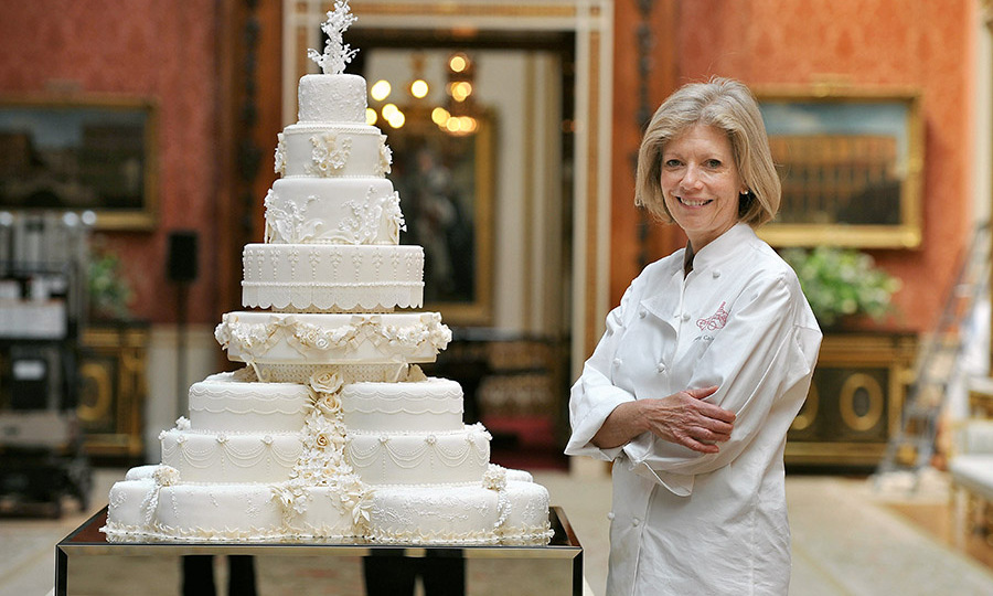 Fiona Cairns stands next to the royal wedding cake for Prince William and Duchess Kate in the Picture Gallery of Buckingham Palace on the day of their wedding. Photo: © John Stillwell/PA Images via Getty Images