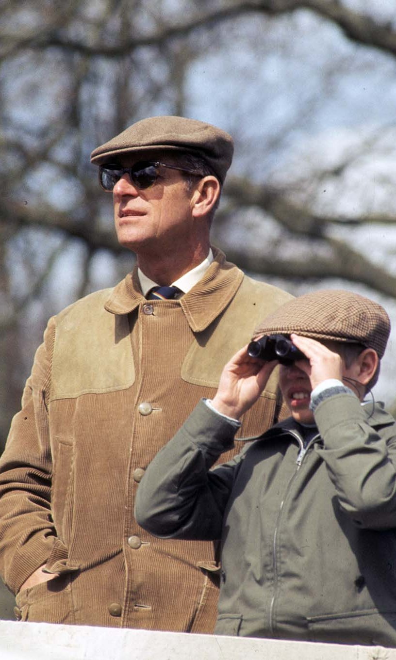 Prince Philip and a young <a href=/tags/0/prince-edward><strong>Prince Edward</strong></a> twinned in caps and casual jackets while taking in the Badminton Horse Trials on April 16, 1977.