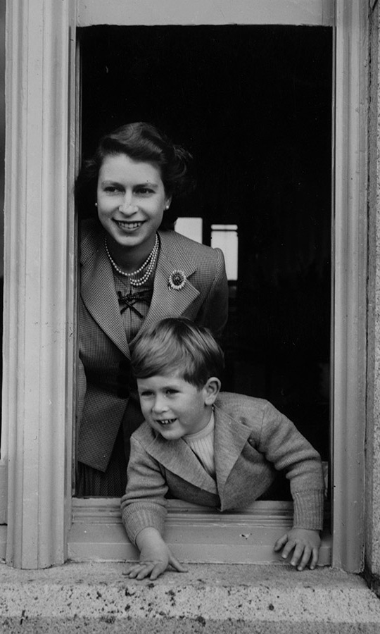 An almost four-year-old <a href=/tags/0/prince-charles><strong>Prince Charles</strong></a> was captured during a sweet moment with his mother as they looked out a window at Balmoral Castle, Scotland in September 1952. 