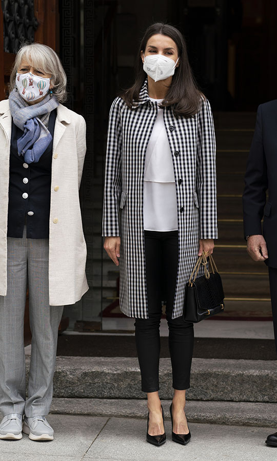 Queen Letizia wowed in a black-and-white check coat, white blouse and black cropped trousers at the headquarters of the Royal Academy of Spanish Language in Madrid on April 27, 2021. 
