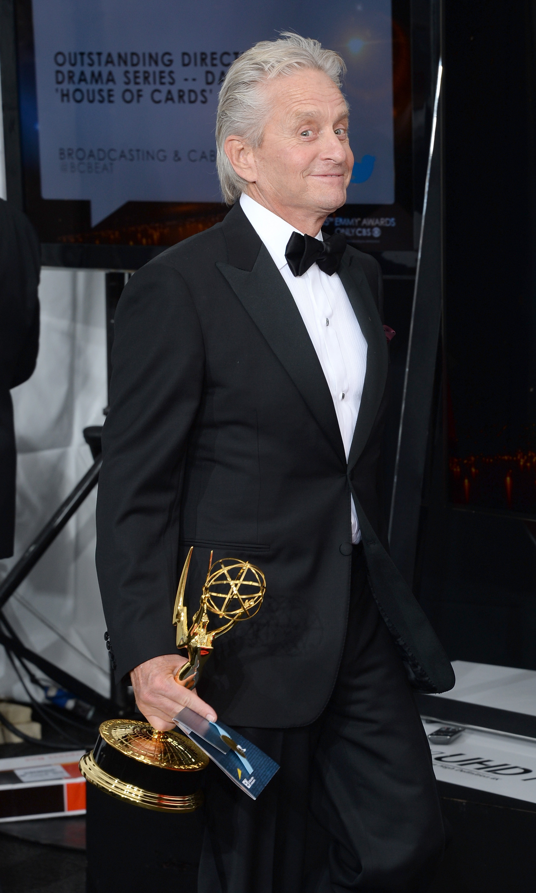 "Michael Douglas is all smiles as he carries his Emmy for Best Lead Actor in a Miniseries or Movie Award for ""Behind The Candelabra""."