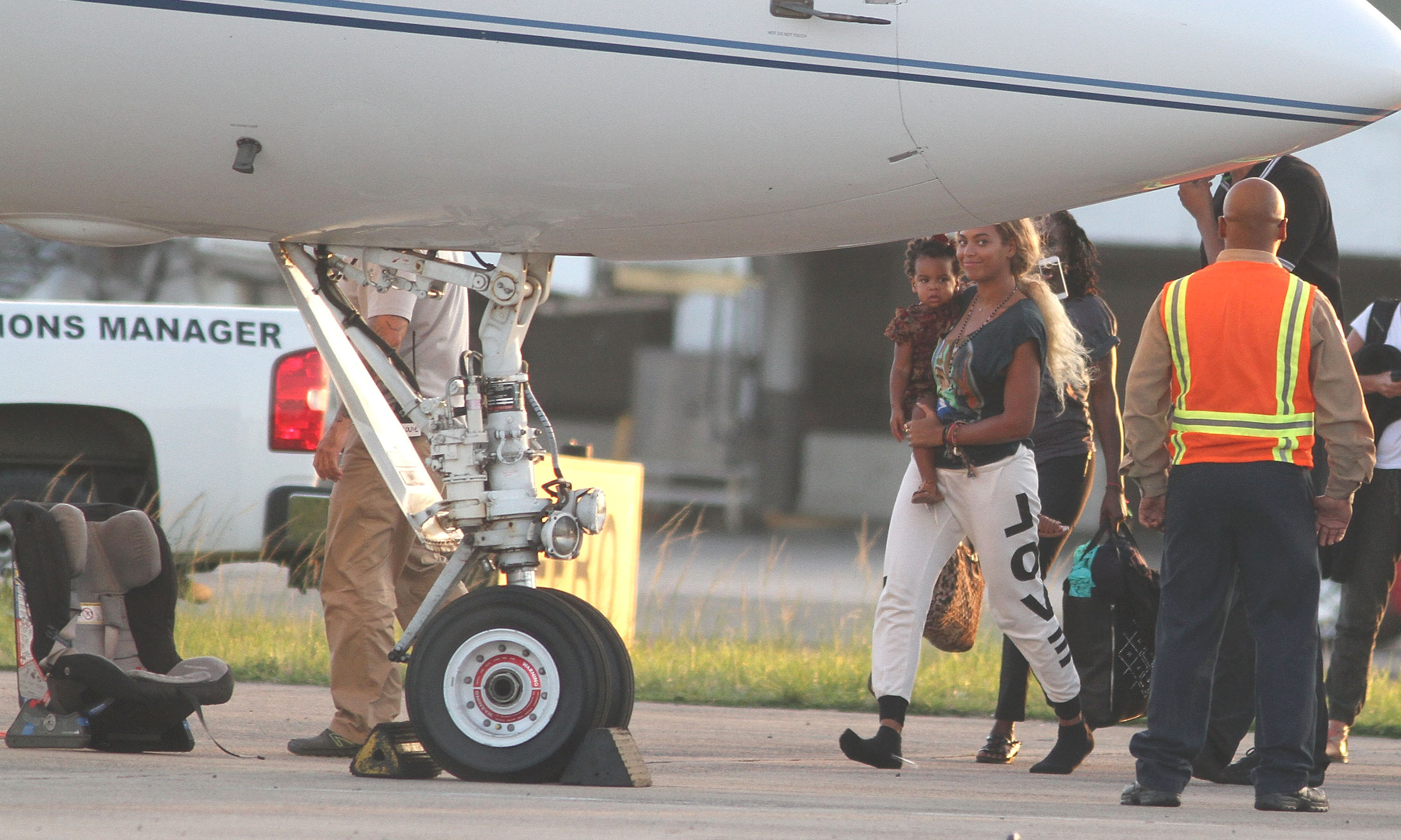 Beyonce shows off her newly long locks carrying 20-month-old, ever-adorable Blue Ivy to a jet in Puerto Rico.