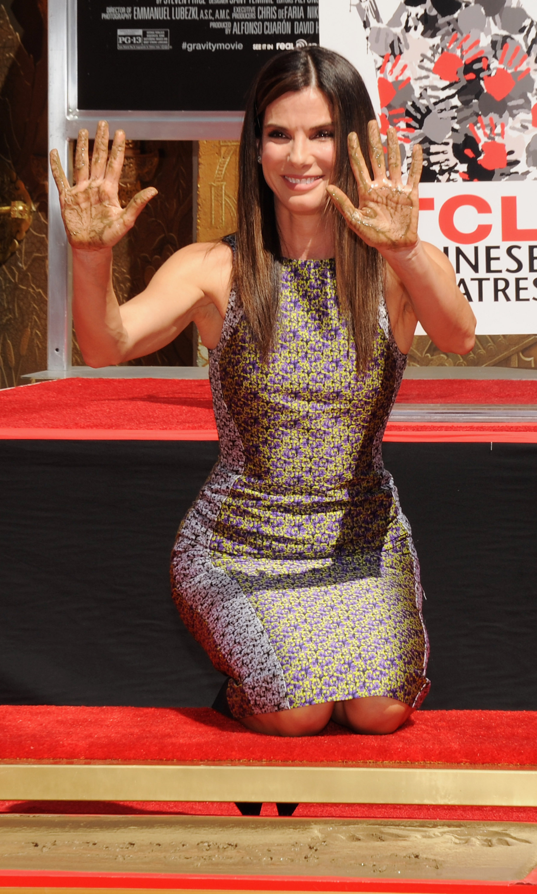 Gravity star Sandra Bullock gets down and dirty digging her hands into a plaque on the Hollywood Walk of Fame at the TCL Chinese Theatre.