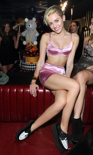 Miley Cyrus attends her album release party for 'Bangerz' on Oct. 8 in New York City, wearing a pink satin bra and high-waisted shorts.