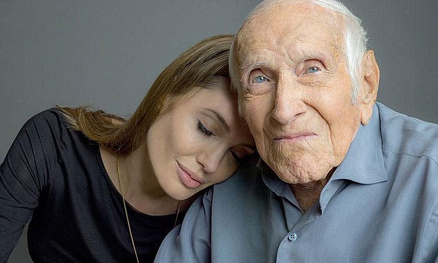 In the first official image from Angelina's new film 'Unbroken,' Angelina Jolie rests her head on war veteran Louis Zamperini. The film tells the story Louis, who survived a plane crash during WWII and floated on a raft for 47 days only to be be picked up by the Japanese and sent to a prisoner of war camp.  Photo credit: Universal Studios