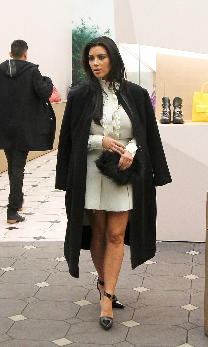 Kim hits the Paris Balanciaga store to do a little high-end shopping on Jan. 11, 2013, sporting a short cream number, which she pairs with a dark wool coat and furry clutch.