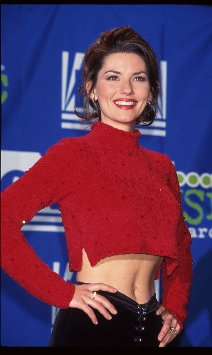 "5. At first, Country Music Television reportedly refused to air the video for her first single, ""What Made You Say That,"" because she showed her midriff. Her second video made headlines too: ""Dance With the One That Brought You"" was directed by Sean Penn. Shania recalls that he gave her $100 just to help her through hard times before her album took off. Here, Shania poses with abs of steel at the 1995 Billboard Music Awards in 1995."