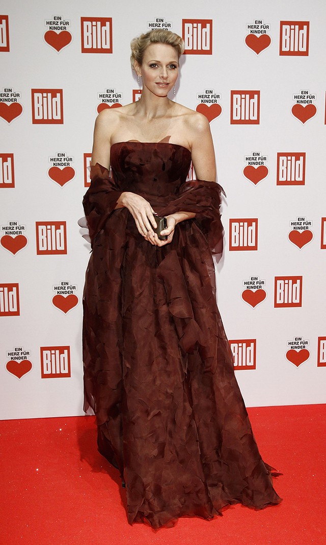 Princess Charlene cuts a regal figure in a sweeping, bordeaux-coloured gown at a 2011 charity gala in Berlin.