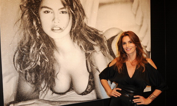 Cindy Crawford proves hasn't aged a day! The 47-year-old poses next to a photo of her younger self as she attends the Art Basel show in Miami, Florida on Dec 3.