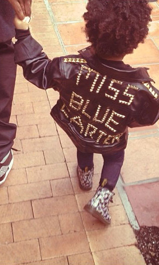 "When you're the daughter of Jay-Z, not just any old jacket will do. For her music mogul dad's birthday, Blue struts her stuff in a leather jacket with gold studs spelling out the words ""Miss Blue Carter."" A pair of floral Doc Marten boots is all she needs to finish off the look. Photo credit: Beyonce/Tumblr"