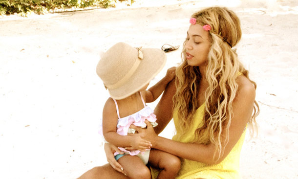 Blue Ivy rocks an adorable frilly top and a stylish sun hat on the beach, while mom channels a bohemian vibe with a floral headband. Photo credit: Beyonce/Tumblr
