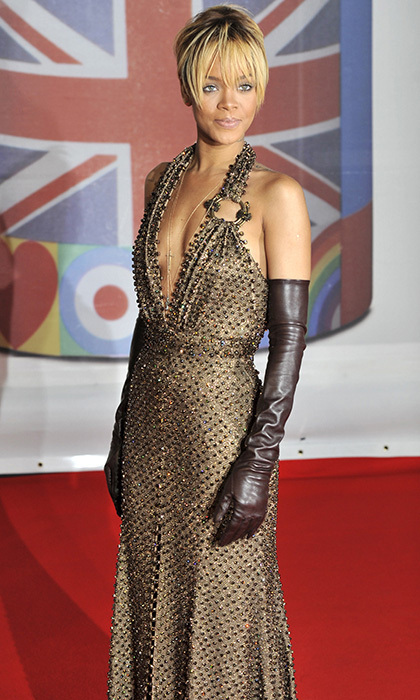"All that glitters was gold in this sequin number by Givenchy Haute Couture. Before receiving her award for International Female Solo Artist at the 2012 Brit Awards, Rihanna dared to bare in this halter-neck gown with revealing décolletage and thigh-high slit. The ""Diamonds"" singer ensured that her look was unique by adding brown leather gloves."