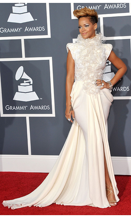 "Rihanna was a vision in white while attending the 2010 Grammy Awards. Before taking the stage to accept her awards for Best Rap Song and Best Rap Collaboration for ""Run This Town,"" the Bajan babe knocked it out of the park once more in this elaborate Elie Saab Couture chiffon dress, which included feather detailing on the bodice, a high collar and draping at the hips."