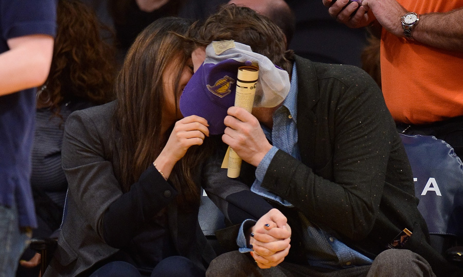 Hands firmly clasped together, the duo engaged in some PDA at a Lakers game in January, using Ashton's baseball cap as a shield for some added privacy. Photo: © Getty