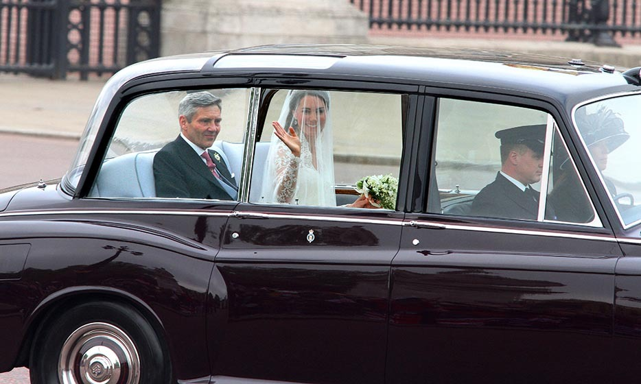 Fans got a first look at the bride as she waved to the crowds while riding in the back of a spiffy Rolls Royce Phantom VI.