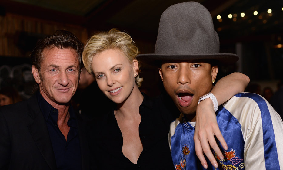 Pharrell Williams looking happy to be with the happy couple, Sean Penn and Charlize Theron. (Photo: Dimitrios Kambouris, Getty Images)