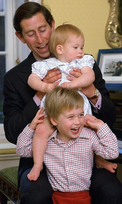 Prince Charles enjoyed some father-son bonding time at Kensington palace with his young sons, lifting Harry onto his big brother's shoulders and laughing with glee.