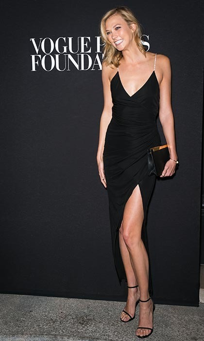 Karlie Kloss struck a pose at the Vogue Paris Foundation Gala in an asymmetrical Saint Laurent dress with jewelled straps, Saint Laurent's Lutetia clutch and Stuart Weitzman's Nudist sandals.