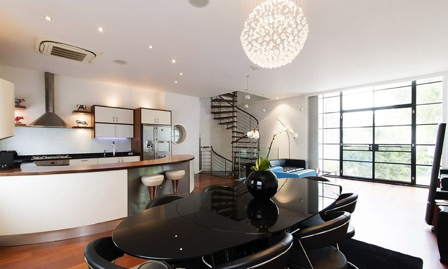 A modern dining table beautifully accents the contemporary kitchen and dining space.