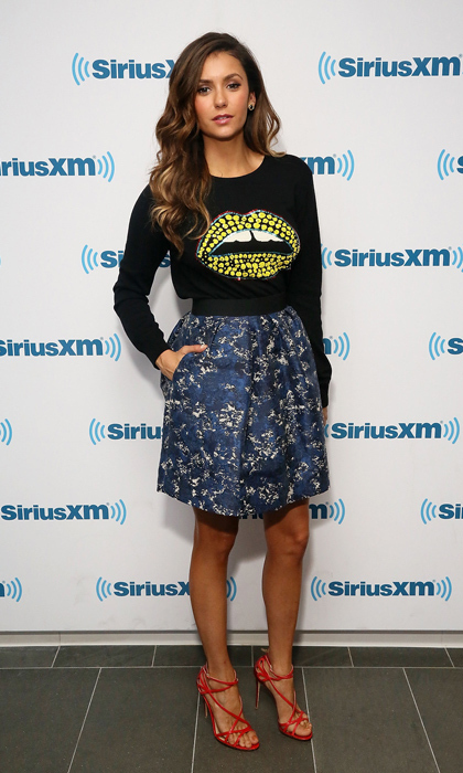 'Vampire Diaries' star Nina Dobrev stopped by the SiriusXFM Studios in NYC wearing a Markus Lupfer statement sweater (inspired by Dutch supermodel Lara Stone) and skirt, plus sultry red Dolce & Gabbana sandals. (Image: Getty)