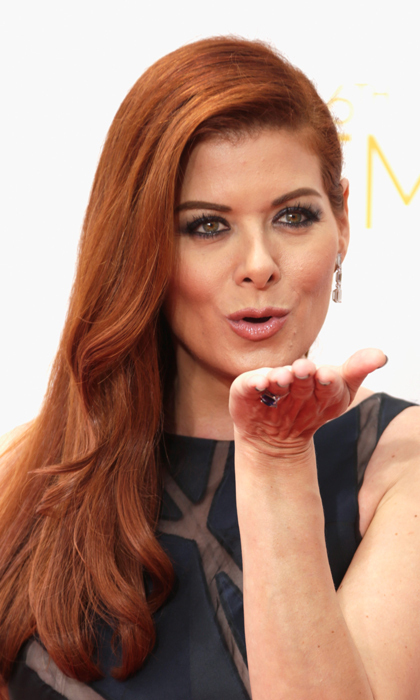 Debra Messing swept her fiery red locks to one side and smiled with her eyes - deeply black-rimmed eyes at that! Lips? Nude, naturally. © Getty