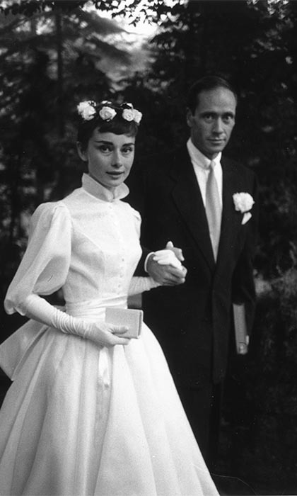 AUDREY HEPBURN AND MEL FERRER: Audrey and her actor husband, Mel Ferrer, were wed on Sept. 25, 1954 at their home in Switzerland in an intimate ceremony that was attended by close friends and family. Audrey was gorgeous in a white Balmain gown paired with a simple garland of flowers on her head, which suited the movie star's simple yet elegant sensibilities to a tee.